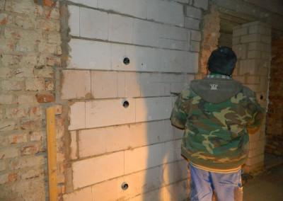 Elektriker beim Ausstemmen der Nische für die Wohnungsunterverteilung