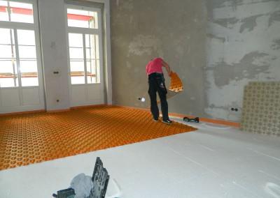 Handwerker beim Verlegen  des Montageunterbaus für die Fußbodenheizung