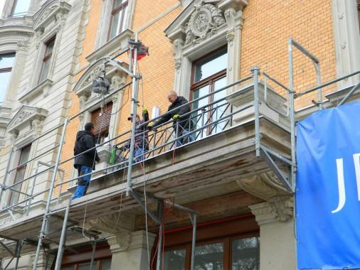 Schlosser beim Anbau der historischen Geländeranlage am Straßenbalkon